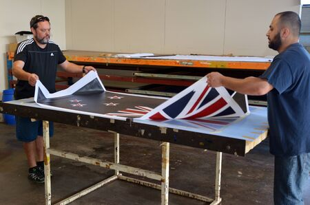 silver fern: AUCKLAND - NOV 24 2015: Workers print the National New Zealand flag. Between 20 Nov and 11 Dec New Zealanders will consider options to their National Flag future.