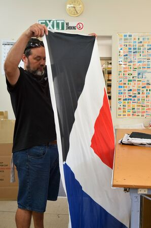 20   24: AUCKLAND - NOV 24 2015: Worker fold the Red Peak flag. Between 20 Nov and 11 Dec New Zealanders will consider options to their National Flag future. Editorial
