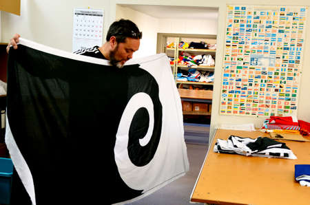 silver fern: AUCKLAND - NOV 24 2015: Worker fold the Koru flag (C). Between 20 Nov and 11 Dec New Zealanders will consider options to their National Flag future.