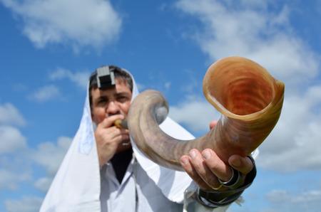 유대인 남자는 로쉬 하 샤나와 욤 키 푸르에서 유대인의 높은 휴일에 야외 하늘 아래 쇼파를 불어 스톡 콘텐츠