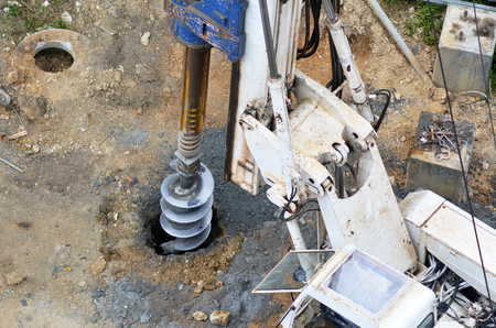 earthmover: Aerial view of hydraulic hammer drilling machine drills a foundation hole at construction site.