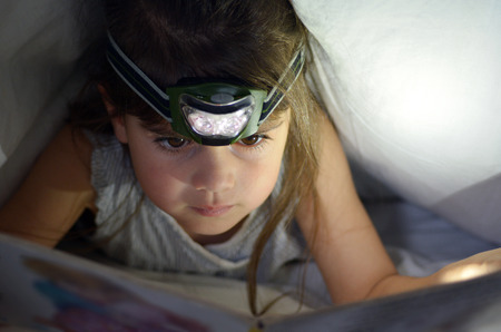 torchlight: Little child (Girl age 5-6) read book in bed under the covers at night. Front view, copy space