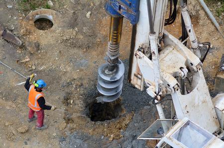건설 현장에서 유압 해머 드릴링 머신에 의해 만들어진 구멍의 깊이 측정 노동자의 공중보기.