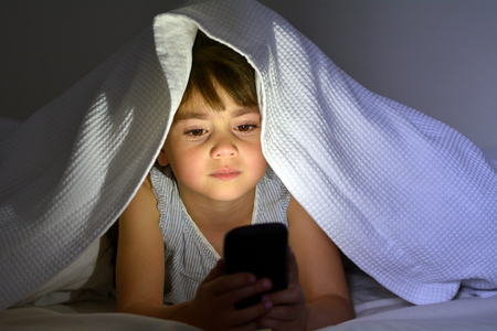 Little child (Girl age 5-6) play on smart phone in bed under the covers at night. Front view, copy space
