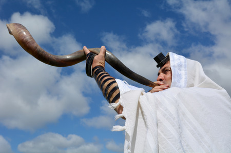 Jewish man blow Shofar outdoors under the sky, on the Jewish High Holidays in Rosh Hashanah and Yom Kippur Stock Photo
