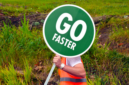 persist: Unrecognizable road worker holds Go Faster traffic road signpost on the way. Conceptual concept and ideas background with copy space.