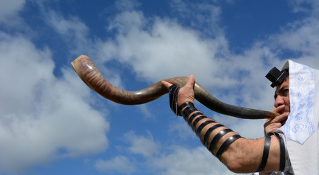 jewish background: Jewish man blow Shofar (Horn) outdoors under the sky, on the Jewish High Holidays in Rosh Hashanah and Yom Kippur Stock Photo
