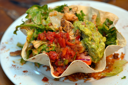 food       plate: Mexican food - tostada salad. Lemon chicken guacamole,salas sauce and  rise in  tortilla.