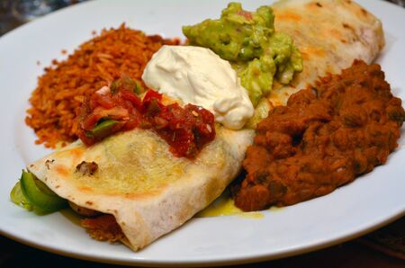 traditional food: Mexican food - burrito served on a plate with guacamole, sour cream,  salsa sauce,  beens and rise