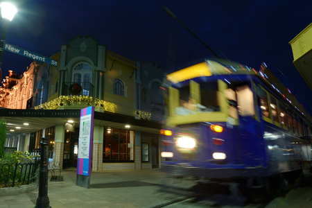 reclaiming: CHRISTCHURCH - DEC 08 2015:Tram pass on New Regent Street at night. Christchurchs beloved New Regent Street is reclaiming its place as a one of the most popular shopping and visitor destination