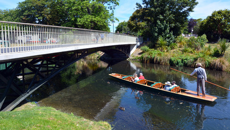 punting: CHRISTCHURCH - DEC 04 2015:People Punting under a bridge spanning over the Avon river Christchurch.It is an iconic tourist attraction of Christchurch, New Zealand.