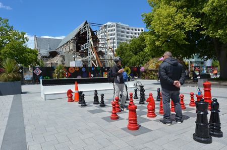 destroying the competition: CHRISTCHURCH,  NZL - DEC 04 2015:People play giant chess in Cathedral Square. About 600,000,000 (Six hundred million) people know how to play chess worldwide Editorial