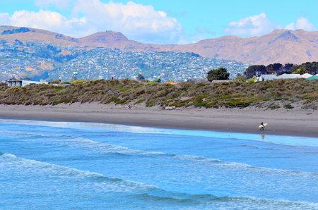 the east coast: CHRISTCHURCH,  NZL - DEC 07 2015:Surfer in New Briton Beach. Its a popular travel destination of sandy beach, with good surfing, stretching 18 km  on the east coast of the south island of New Zealand