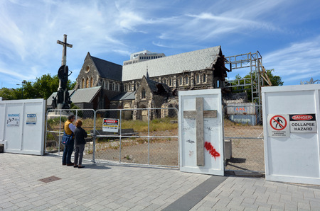 severely: CHRISTCHURCH - DEC 04 2015:Visitors at ChristChurch Cathedral.The 2011 Christchurch earthquake destroyed the spire and part of the tower, and severely damaged the structure of the remaining building. Editorial
