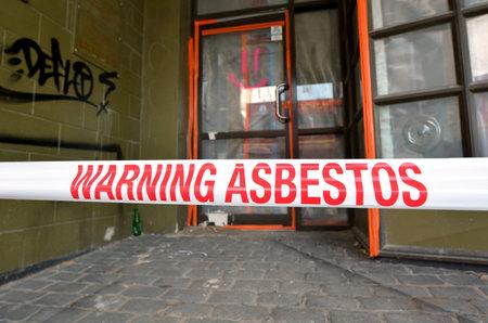CHRISTCHURCH - DIC 04 2015: La muestra lee: Advertencia - Eliminación de amianto en progress.Inhalation de fibras de amianto puede causar enfermedades graves y mortales, incluyendo cáncer de pulmón, mesotelioma y asbestosis. Foto de archivo - 49377654