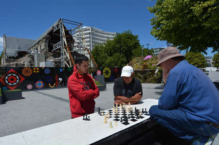 destroying the competition: CHRISTCHURCH,  NZL - DEC 04 2015:People play Chess in Cathedral Square. About 600,000,000 (Six hundred million) people know how to play chess worldwide