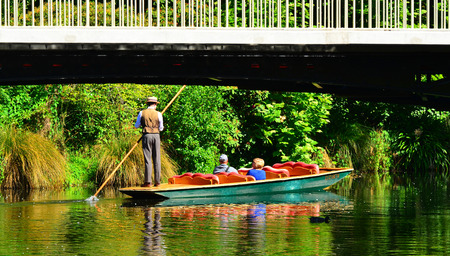 punting: CHRISTCHURCH,  NZL - DEC 08 2015:People Punting under a bridge spanning over the Avon river Christchurch.It is an iconic tourist attraction of Christchurch, New Zealand. Editorial