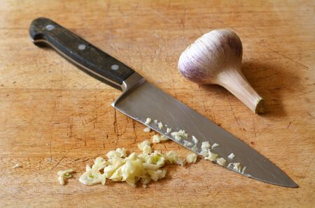 cuchillo de cocina: Chopped garlic on a wooden board, with kitchen knife.