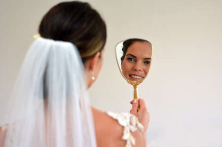 self image: Young bride looks at herself in the mirror on her Wedding Day. Woman,self esteem, self image, wedding and marriage concept. copy space