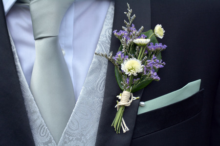 corsage: Corsage boutonniere brooch on a man groom suit on wedding day. Wedding men fashion Stock Photo