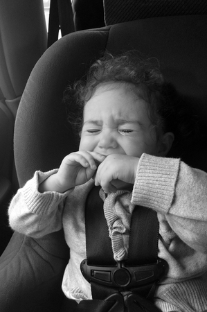 buckled: Child (girl age 1-2) cry in a car seat. Childhood and children behaviour education concept Stock Photo