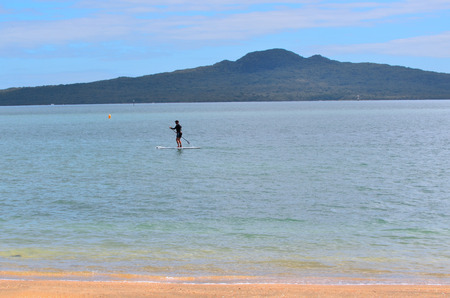 distances: AUCKLAND - JAN 11 2016:Person paddle boarding in mission bay in Auckland New Zealand.Its an emerging global sport with a Hawaiian heritage.Its an ancient form of surfing for longer distances.