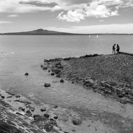 hectares: AUCKLAND - JAN 11 2016:Couple with Rangitoto Island. It is the most recent and the largest (2311 hectares) of the approximately 50 volcanoes of the Auckland volcanic field