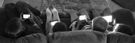 suggests: AUCKLAND -  JAN 14 2016:Teenagers play on electronic devices.New study suggests that spending too much time using electronic devices during the day harms teens sleep at night.
