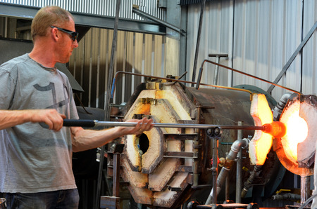 producing: TAUPO, NZL - JAN 14 2016:Glass blower shaping molten glass.Glassblowing craft was passed from master to apprentice and at times in history, the penalty for disclosing secret techniques was death!