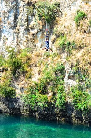 bungee jumping: TAUPO, NZL - 14 de enero de 2016: Persona durante el salto bungy de 47 metros (154 pies) en por encima del río Waikato en Taupo, Nueva Zelanda. Editorial