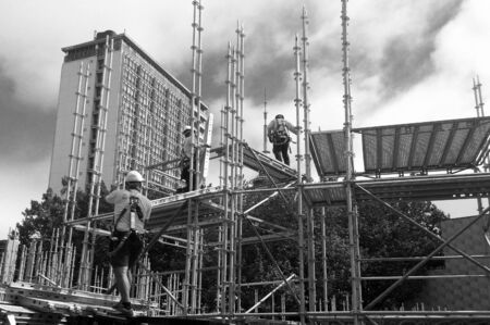 deficiencies: AUCKLAND -  JAN 09 2016: Scaffold builders at work.OSHA statistics report that about 28% of the scaffold accidents that occur are the result of construction deficiencies.