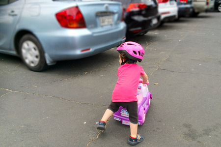 AUCKLAND - JAN 11 2016:Little girl (Naomi Ben-Ari age 1-2) rid a toy car in parking lot. The U.S. Center for Disease Control reported that about 300 fatalities per year result from backup collisions.