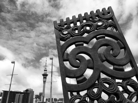 migrated: AUCKLAND,  NZL - JAN 04 2015:Maori wood curving against Auckland  skyline.Maori are the indigenous people of New Zealand. Originally from Polynesia, Maori migrated to New Zealand over 1000 years ago.