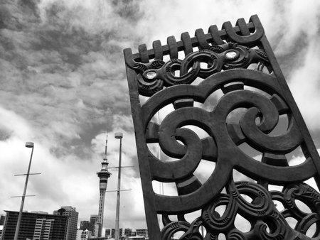maories: AUCKLAND, NZL - ENE 04 2015: maor� curvar la madera contra el Auckland skyline.Maori son el pueblo ind�gena de Nueva Zelanda. Originario de la Polinesia, maor� emigr� a Nueva Zelanda hace m�s de 1000 a�os. Editorial