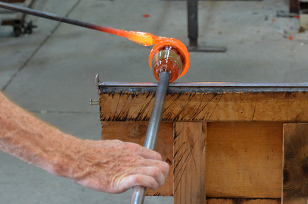 glasswork: TAUPO, NZL - JAN 14 2016:Glass blower shaping molten glass.Glassblowing craft was passed from master to apprentice and at times in history, the penalty for disclosing secret techniques was death!