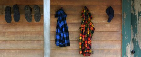 hunter's cabin: Hiking shoes and warm clothes hang outside an old mountain cabin. Mountain holiday vacation concept