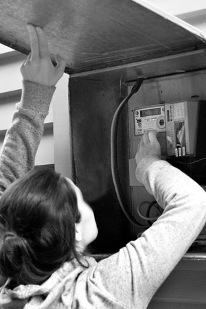 AUCKLAND - DEC 06 2015: A woman checks her smart meter. The safety of smart meters raised concerns, mainly because they give off the same kinds of radiofrequency RF waves as cell phones and Wi-Fi devices.