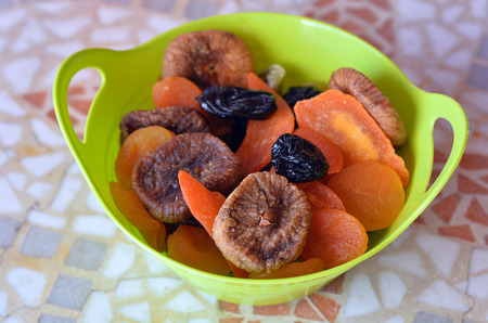 shvat: Mix of dried fruits in a green bowl during the Jewish holiday Tu Bishvat. Food background and texture
