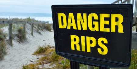 currents: Danger rips of strong currents sign posted on the beach. copy space concept conceptual.
