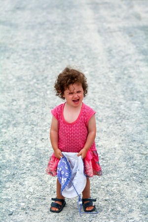 misbehaving: Little girl (age 1-2) having a tantrum screaming alone on a gravel road during holiday travel vacation.Childhood concept with copy space