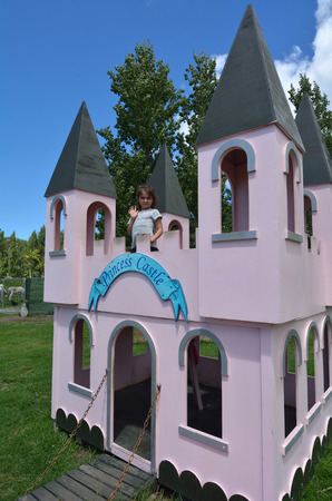 pretend: Little girl age (5-6) play pretend to be a princes in outdoor playground princes castle.