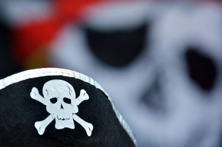 jolly roger: Pirate hat with skull and bones sign and Jolly Roger flag in the background.