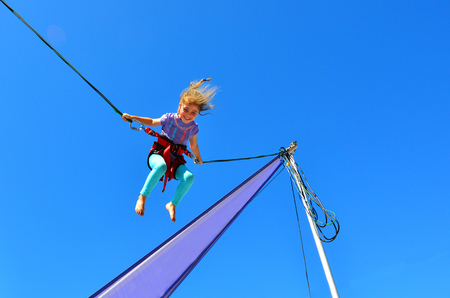 Little girl age 5-6 on Bungee trampoline. Concept risk with copy space Foto de archivo
