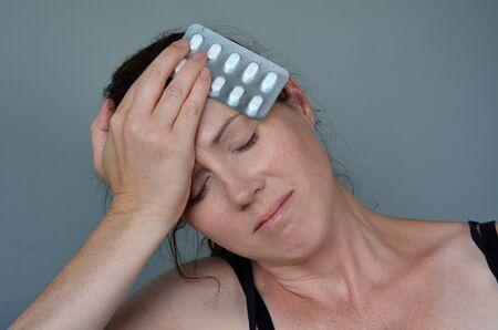 Woman (age 30-40) having headache taking pills. Helath concept