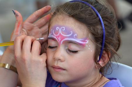 meisje leeftijd 5-6 krijgt haar gezicht beschilderd met een kroon als een princes door schminken kunstenaar.