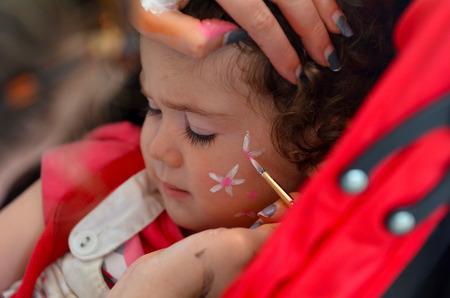 Toddler girl age 1-2 getting her face painted with flowers by face painting artist. Stock Photo