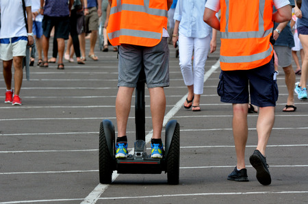 a two wheeled vehicle: AUCKLAND,  NZL - JAN 30 2016:Man ride Segway PT in crowded place.Segway PTs can reach a speed of 12.5 miles per hour 20.1 kmh.