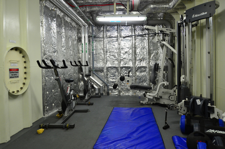exercice: AUCKLAND - JAN 30 2016:Gym room on a Naval ship.Us Navy physical fitness test consists 1.5 mile run, sit-ups, push-ups, swimming 500m and 1.5 mile run.This PT is used by many law enforcement agencies Editorial