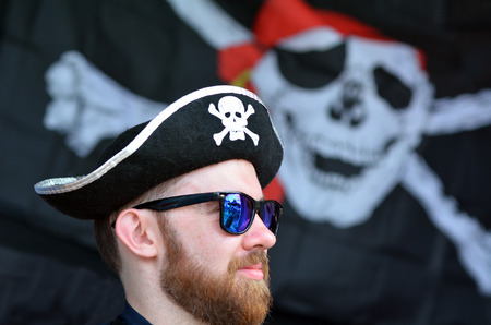 commits: AUCKLAND - JAN 30 2016:Man dressed up as a pirate.A pirate is a person who commits a crime while at sea and pirates didnt actually use a Jolly Roger as their flag, Instead, they just used black flags