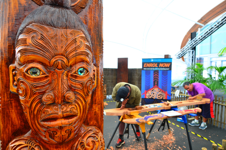 migrated: AUCKLAND,  NZL - JAN 30 2016:Maori men carve a Maori Wood carving. Maori are the indigenous people of New Zealand. Originally from Polynesia, Maori migrated to New Zealand over 1000 years ago.